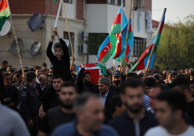 Pessoas carregam caixão de membro das Forças Armadas do Azerbaijão que foi supostamente morto durante combates pela região separatista de Nagorno-Karabakh, durante um funeral no distrito fronteiriço de Tartar, Azerbaijão, 29 de setembro de 2020