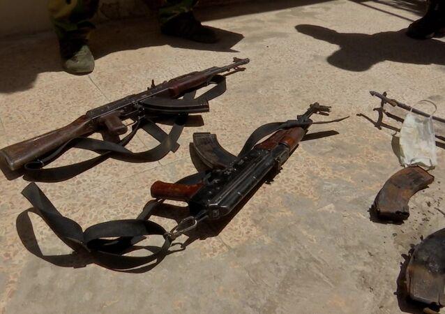 Armas abandonadas e máscara protetora no chão na cidade Tadmor, na Síria, 14 de setembro de 2020