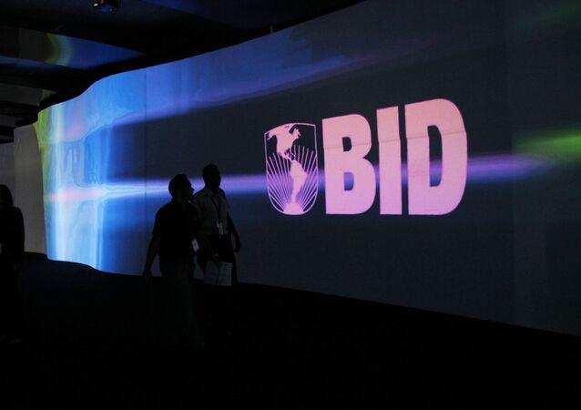 Visitantes caminham em frente ao logo do Banco Interamericano de Desenvolvimento (BID).