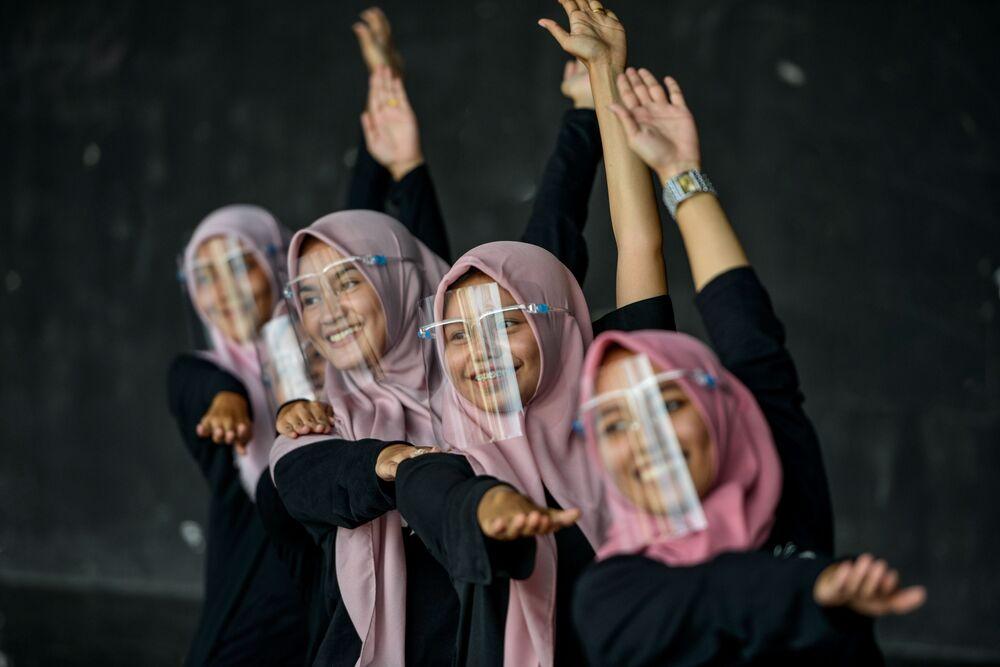 Garotas com máscaras para se protegerem do coronavírus praticam dança em centro cultural na Indonésia