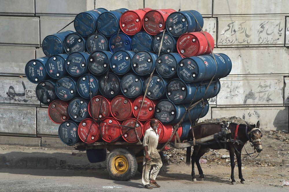 Homem passa ao lado de cavalo e carroça carregada com barris, no Paquistão