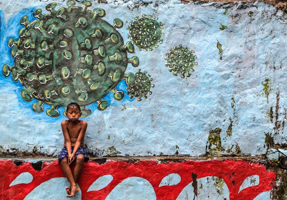 Garoto sentado diante de mural com desenho do vírus responsável pela COVID-19 em Bogor, na Indonésia