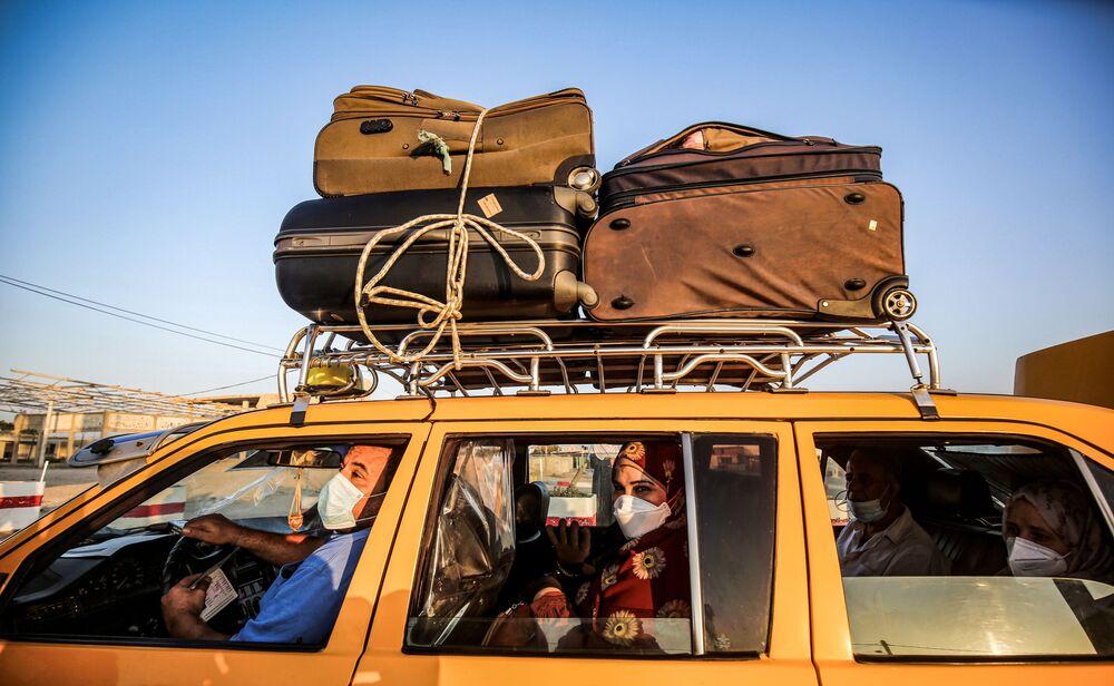 Taxista palestino e passageiros, com máscaras para se protegerem da propagação da COVID-19, passam por Rafah
