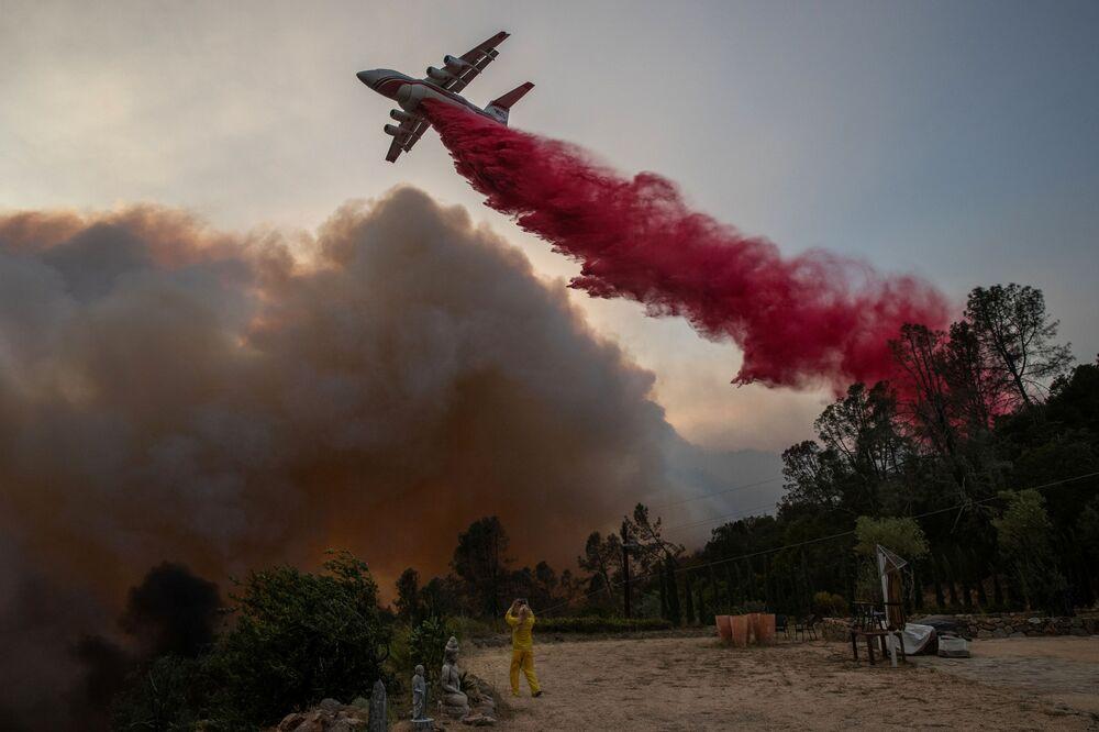 Mulher usando traje resistente ao fogo fotografa aeronave despejando retardador de fogo em vinhedo afetado por incêndio na Califórnia