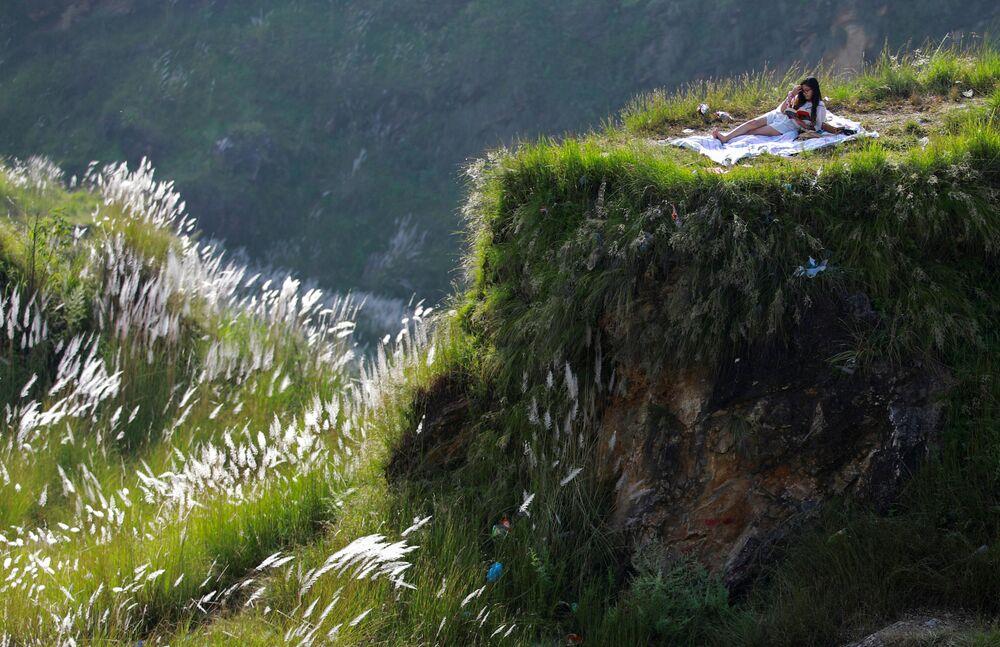 Mulher lê livro durante piquenique na capital do Nepal