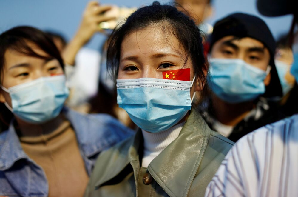Chinesas com máscaras participam de cerimônia de hasteamento da bandeira pelo 71º aniversário da proclamação da República Popular da China
