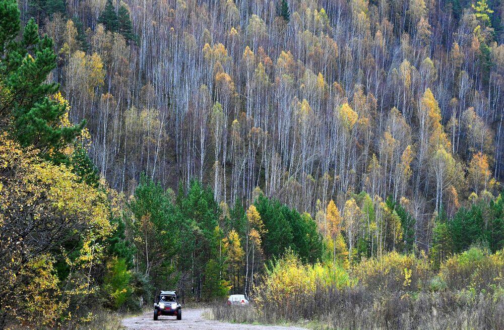 Veículo quadriciclo passa por estrada que atravessa a taiga na Sibéria