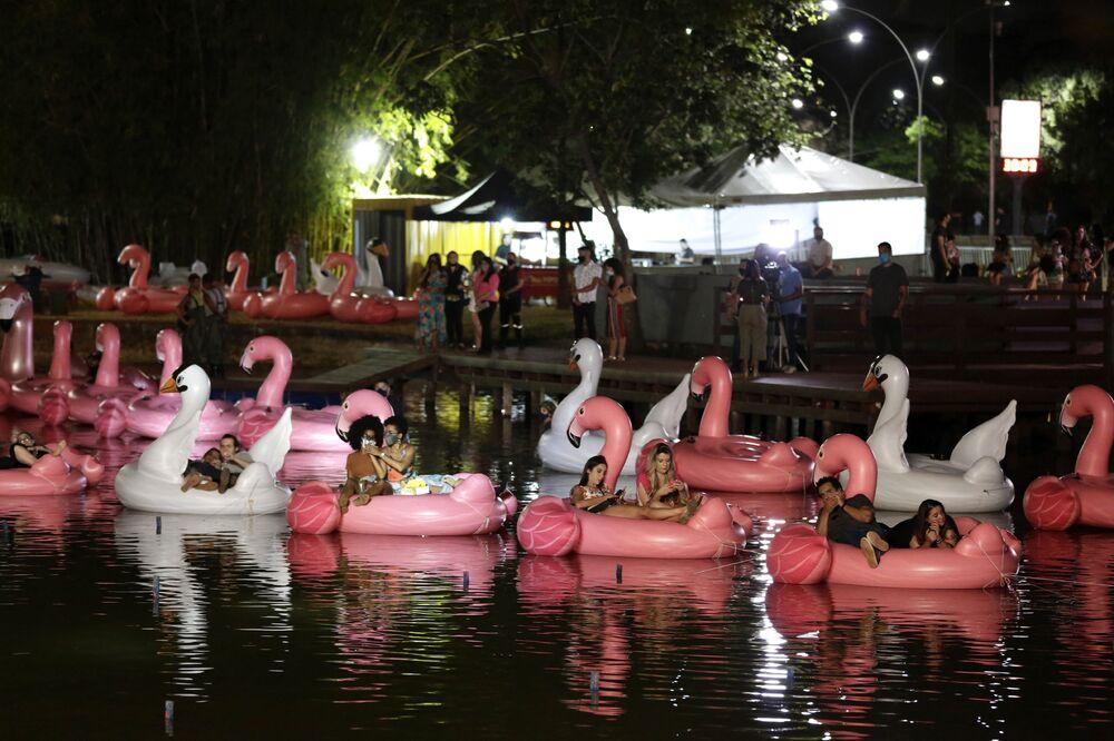 Pessoas relaxando em flamingos e cisnes infláveis, no Parque da Cidade Sarah Kubitschek, assistindo a um filme no decorrer do Festival Flutua, o primeiro festival flutuante do país, em Brasília, 30 de setembro de 2020