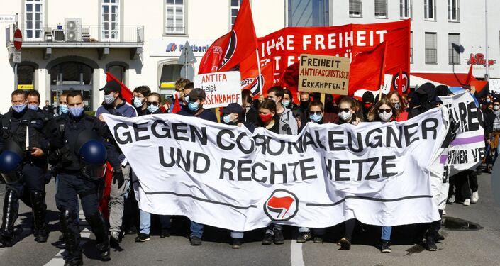 Em Konstanz, na Alemanha, policiais caminham ao lado de manifestantes contrários aos protestos que contestam as restrições sociais impostas pelo governo alemão em meio à pandemia da COVID-19, em 4 de outubro de 2020.