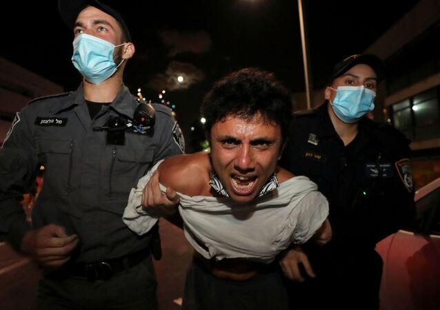 Em Tel Aviv, Israel, policiais detém um manifestante em meio a um protesto contra o governo, que estabeleceu regras de distanciamento social contra a COVID-19 proibindo que cidadãos realizem manifestações longe de suas casas, em 3 de outubro de 2020
