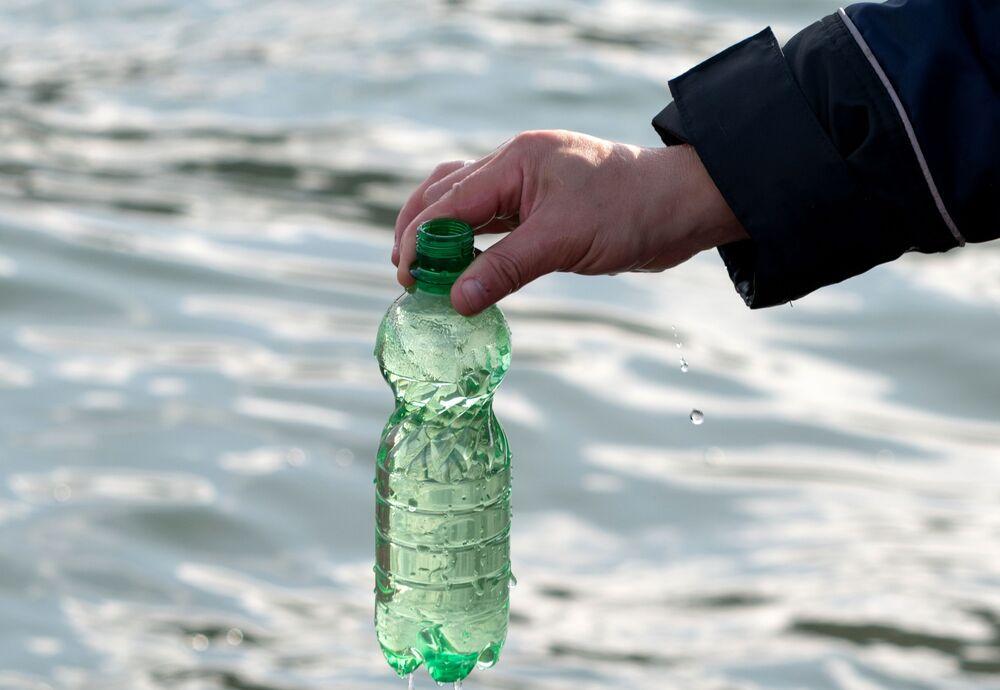 Membro do Comitê de Investigação da Rússia na região de Kamchatka recolhe amostra de água do mar em garrafa