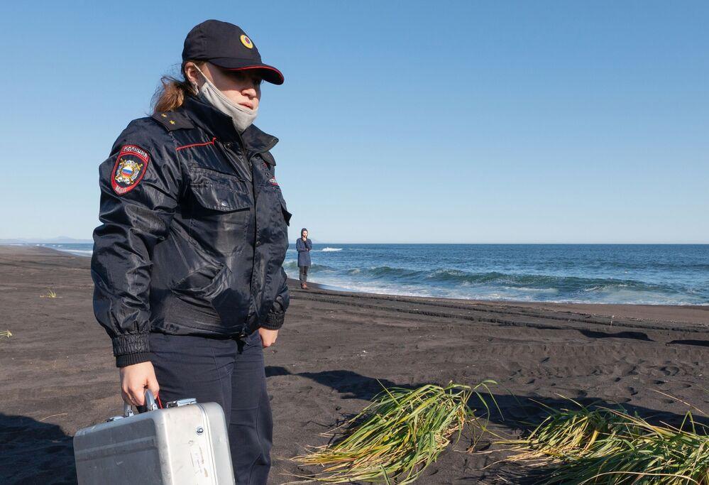 Policial passa por praia enquanto ocorre a coleta de amostras do incidente em Kamchatka, na Rússia