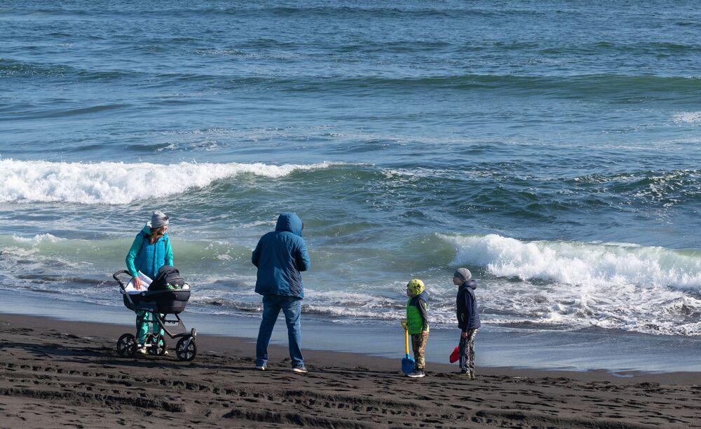 Família brinca em praia de Kamchatka banhada pelo oceano Pacífico