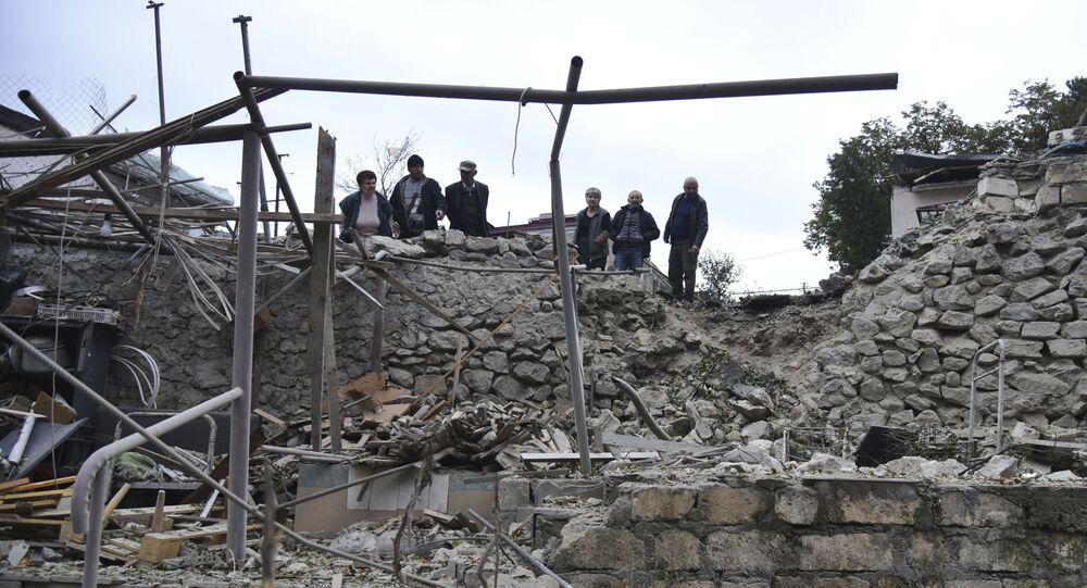 Homens observam destruição em Stepanakert, na república não reconhecida de Nagorno-Karabakh, após ataques de artilharia