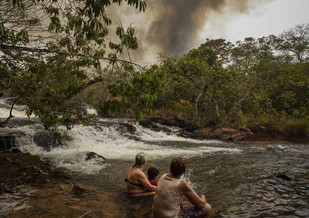 Turistas se banham em uma cachoeira do rio Mutum no município de Santo Antonio de Leverger, enquanto um incêndio florestal destrói a vegetação ao redor.