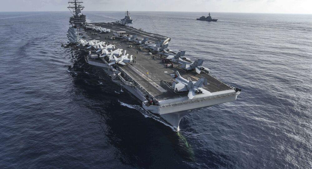 Porta-aviões USS Ronald Reagan, na frente, e o destróier de mísseis guiados USS Milius, no entro, conduzem um exercício com navios da Força Marítima de Autodefesa do Japão no mar do Sul da China, 31 de agosto de 2018