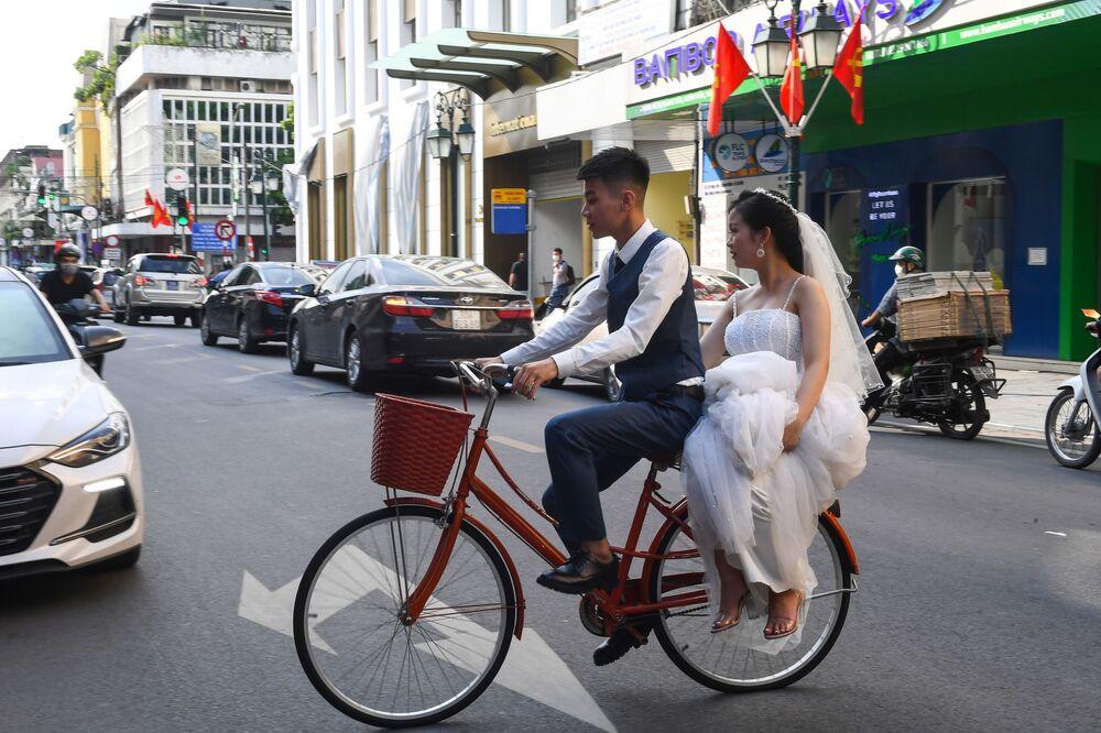 Noivo leva sua jovem esposa de bicicleta em Hanói, Vietnã