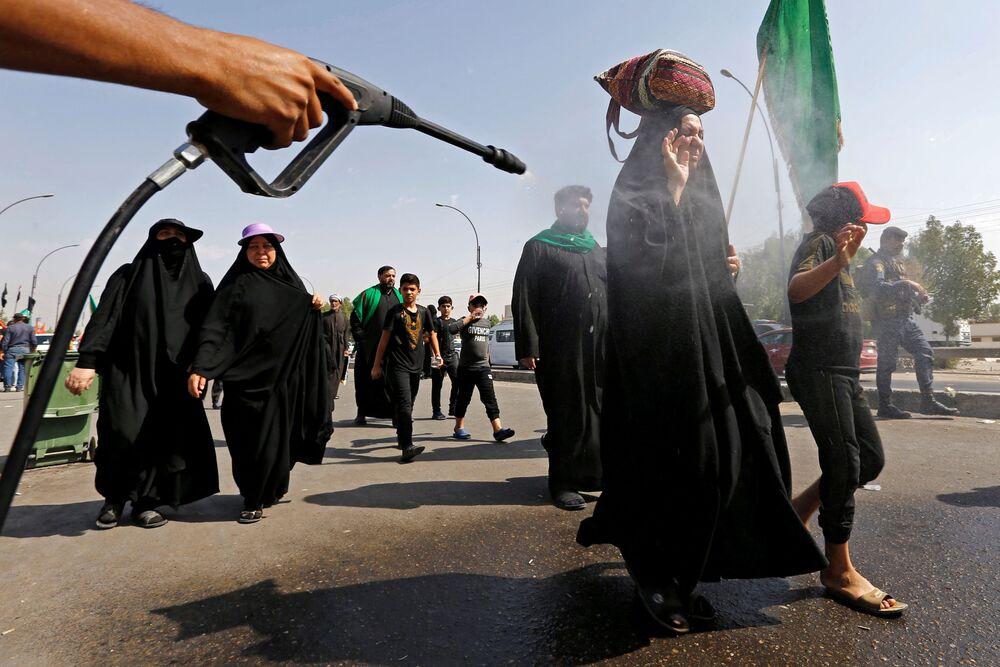 Peregrinos muçulmanos xiitas iraquianos são pulverizados com água para esfriar enquanto caminham à cidade sagrada de Kerbala