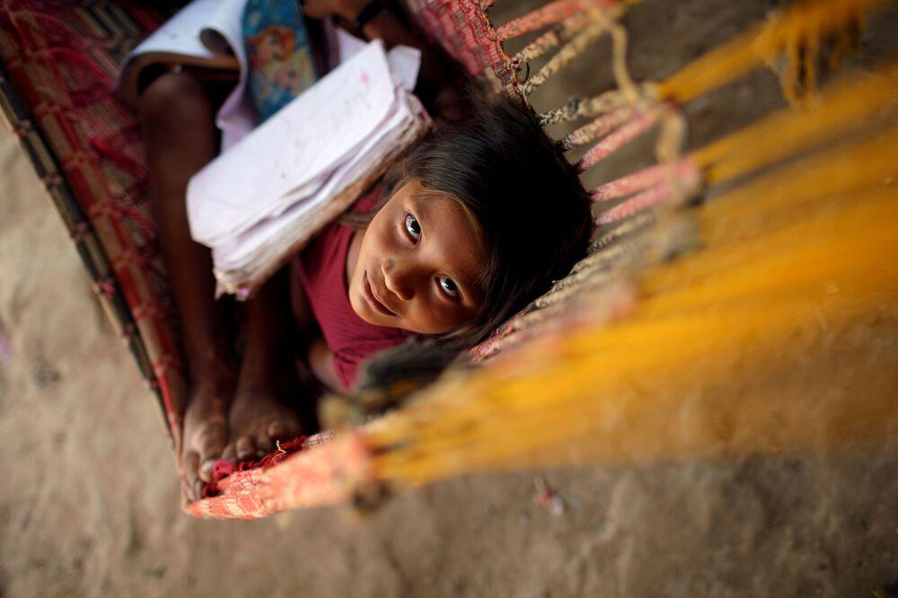 Criança da etnia indígena Guajajara do Brasil descansa em cama de rede na aldeia de Urucu-Juruá, Maranhão, Brasil
