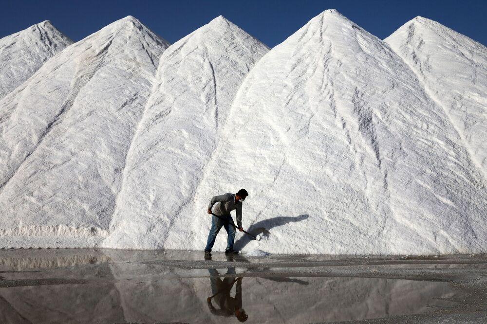 Trabalhador de uma fábrica de sal junta grandes pilhas de sal no lago Tuz, na Turquia