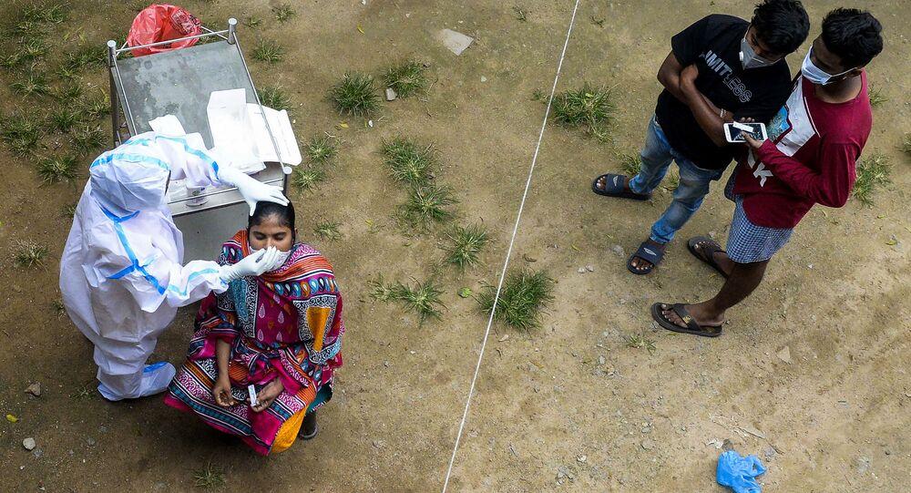 Profissional de saúde coleta esfregaço de uma mulher para executar teste de coronavírus nos arredores de Hyderabad, Índia