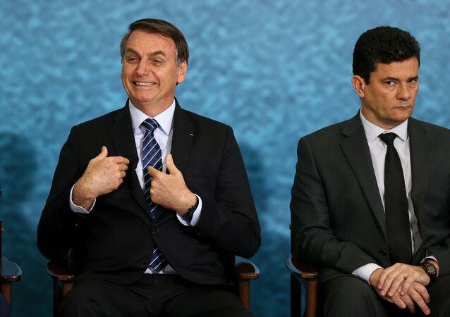Em Brasília, o presidente Jair Bolsonaro (à esquerda) gesticula ao lado do então ministro da Justiça e Segurança Pública, Sergio Moro (à direita),  durante cerimônia de divulgação do pacote anticrime, em 3 de outubro de 2019