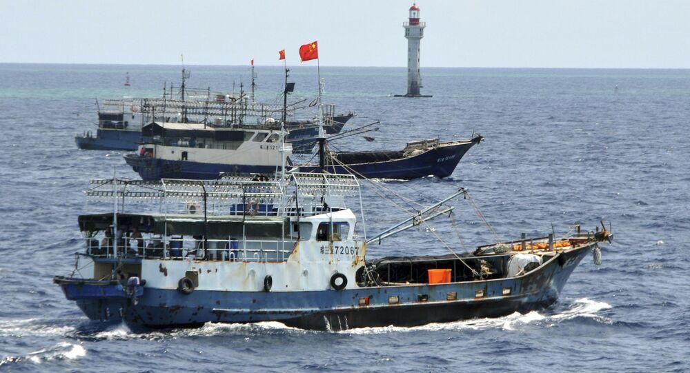 Navios de pesca chineses navegam perto de um farol no recife de Zhubi, nas ilhas Spratly, no mar do Sul da China, em 18 de julho de 2012