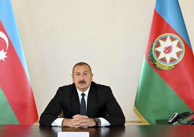 Presidente do Azerbaijão, Ilham Aliev, ao lado de bandeiras do país
