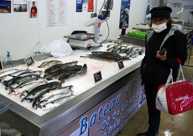 No porto de Cibourne, sul da França, uma mulher com máscara protetora contra a COVID-19 compra peixes em um barco pesqueiro, em 28 de abril de 2020