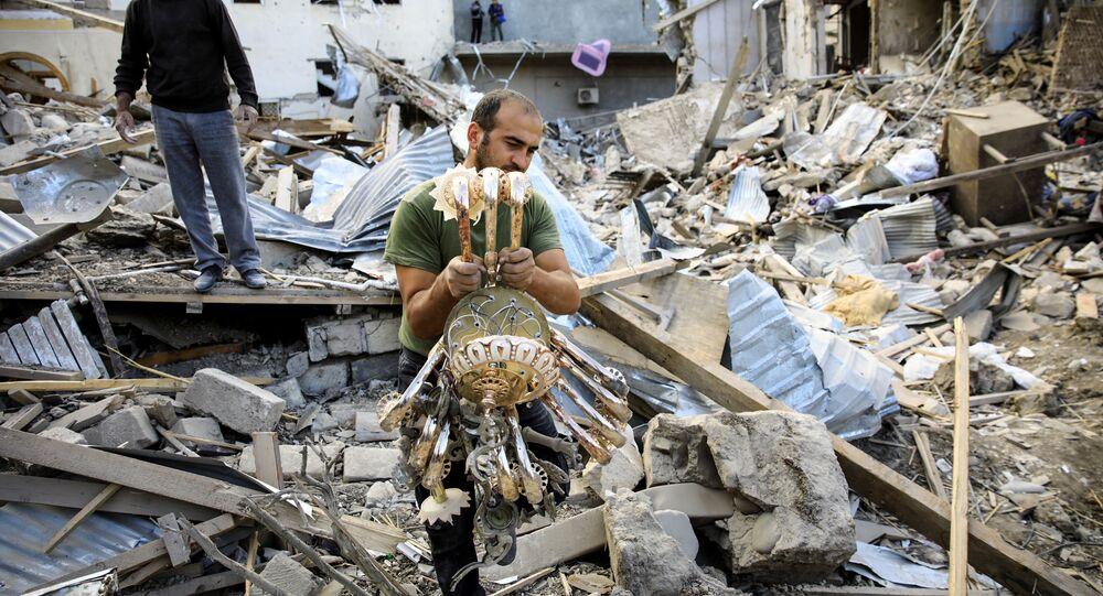 Homem carrega candelabro em Ganja, cidade da república não reconhecida de Nagorno-Karabakh atingida por um foguete