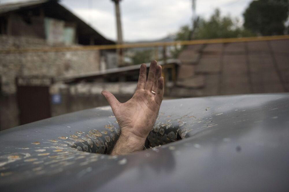 Mão se estende através de buraco deixado em carro por bombardeio à cidade de Stepanakert, em Nagorno-Karabakh