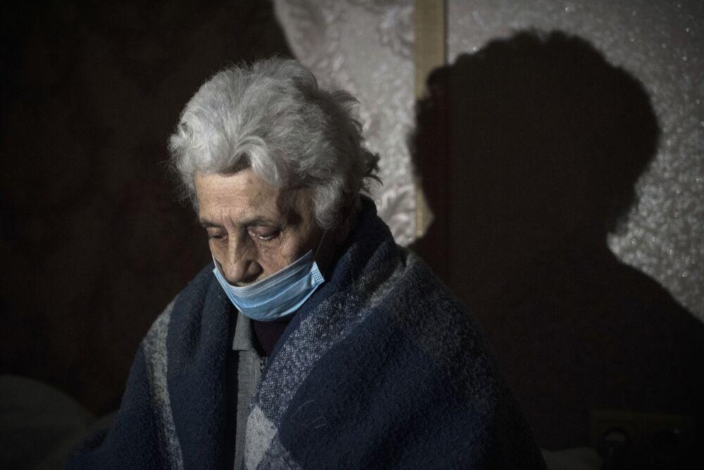 Idosa com máscara se protege de ataques a Stepanakert em porão de casa
