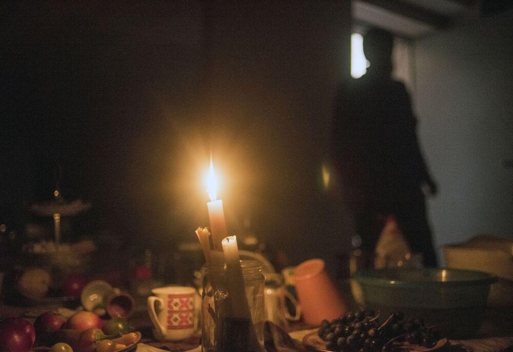 Homem se protege em porão de casa, onde pessoas se refugiam de ataques à cidade de Stepanakert