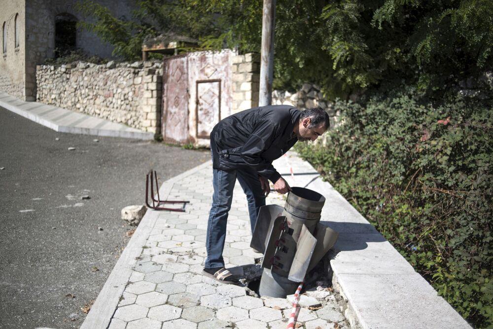 Morador de Martuni observa projétil não explodido lançado contra a cidade de Nagorno-Karabakh