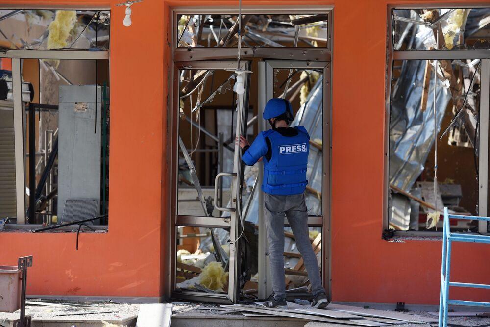 Jornalista abre porta de loja destruída por ataque na cidade de Martakert, em Nagorno-Karabakh