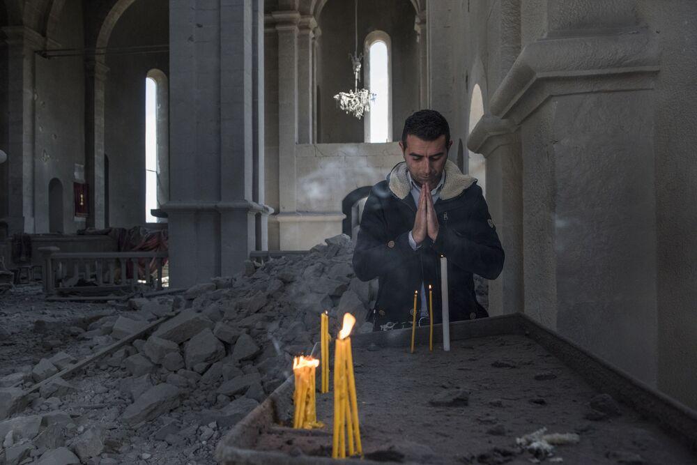 Homem reza em igreja destruída por bombardeio à cidade de Shusha, em Nagorno-Karabakh