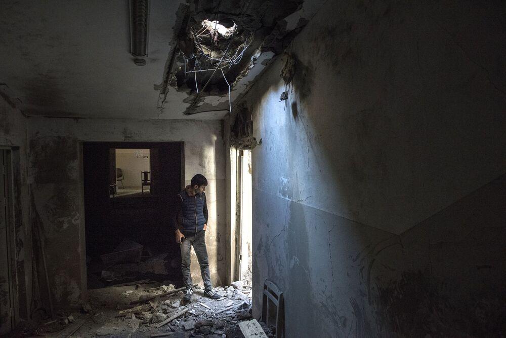 Homem passa por casa, afetada por bombardeio das Forças Armadas do Azerbaijão, na cidade de Shusha
