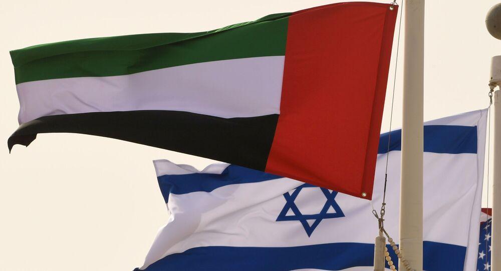 Bandeiras dos Emirados Árabes Unidos, de Israel e dos EUA balançam ao vento no aeroporto de Abu Dhabi, na chegada do primeiro voo comercial de Israel para os Emirados Árabes Unidos, 31 de agosto de 2020