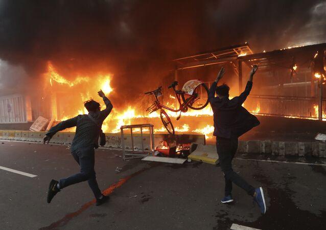 Em Jacarta, manifestantes jogam bicicletas em uma estação de metrô em chamas durante protesto na capital da Indonésia, em 8 de outubro de 2020