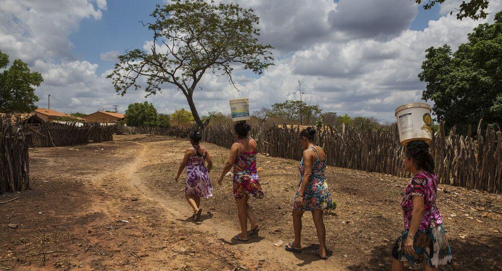 Mulheres carregam baldes de água em do povoado de Queimadas do Angico, em Guaribas, no interior do Piauí, principal reduto de votos petistas no país no primeiro turno das eleições de 2018