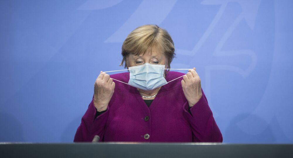 Em Berlim, a chanceler alemã Angela Merkel manuseia sua máscara na chegada a uma coletiva de imprensa após encontro com governadores estaduais do país, em 14 de outubro de 2020
