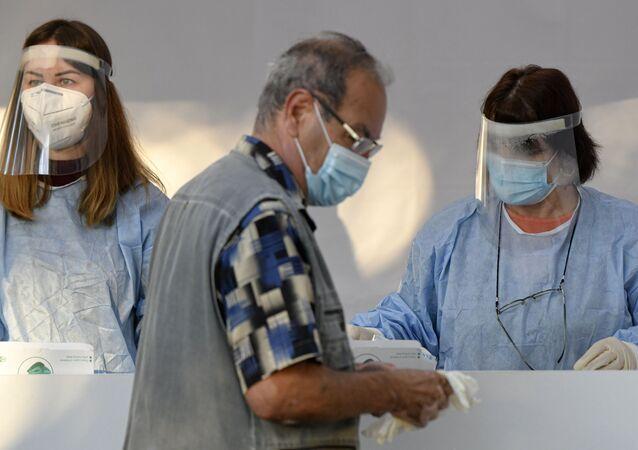 Em Bucareste, na Romênia, um homem usa máscara como proteção contra a COVID-19 após ter a temperatura tomada antes de votar, em 27 de setembro de 2020