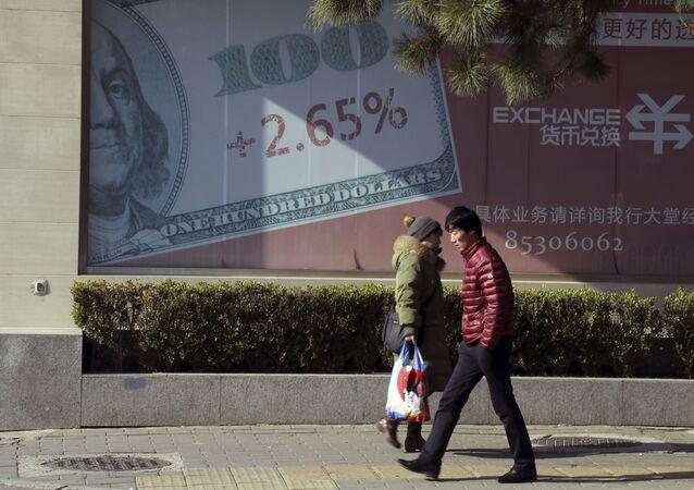 Pessoas passam diante de publicidade de compra e venda de dólares em Pequim, na China