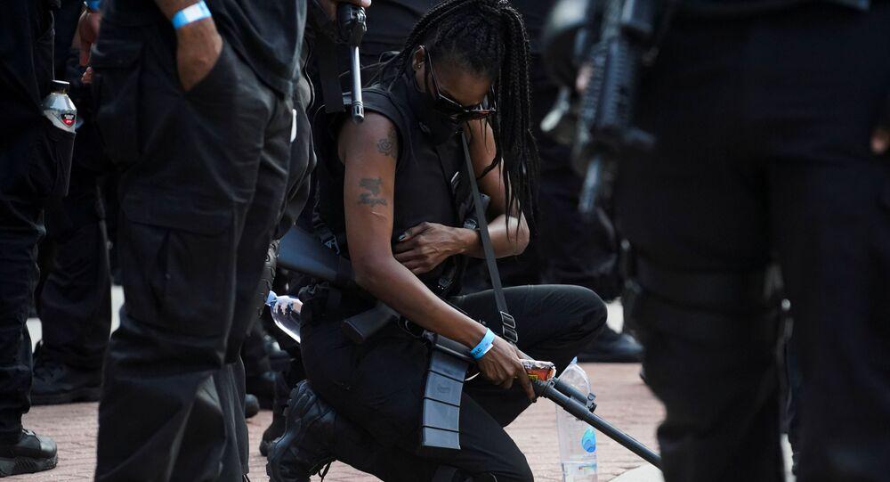 Membro da milícia negra NFAC se ajoelha durante manifestação em Lafayette, Louisiana (EUA), 3 de outubro de 2020