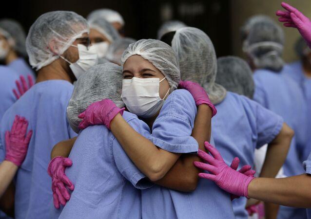 Agentes de saúde celebram após último paciente de COVID-19 receber alta de hospital de campanha em Brasília, 15 de outubro de 2020