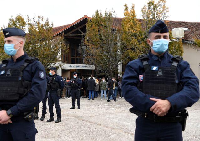 Em Conflans Sainte-Honorine, na França, policiais fazem guarda em frente enquanto levam flores ao local onde um professor de História foi assassinado, em 16 de outubro de 2020