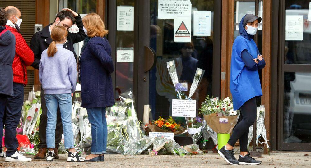 Pessoas trazem flores para o colégio Bois d'Aulne após o ataque no subúrbio de Conflans St. Honorine, França, 17 de outubro de 2020