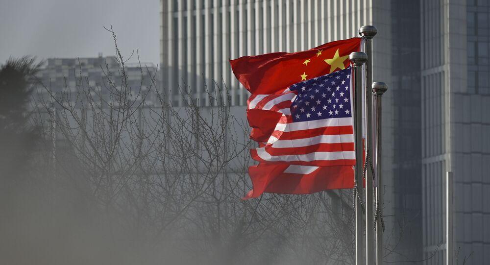 Bandeiras nacionais da China e EUA na entrada de edifício de escritórios de uma empresa em Pequim, China, 19 de janeiro de 2020