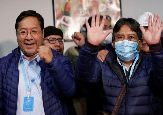 Candidato a presidente Luis Arce do MAS acena com o candidato a vice-presidente David Choquehuanca, que usa uma máscara protetora durante eleições presidenciais na Bolívia