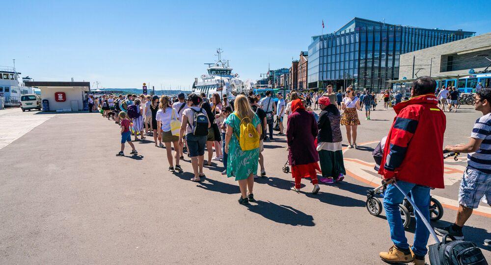 Pessoas fazem fila no cais da Prefeitura em Oslo antes de pegar barcos para chegar às ilhas no fiorde de Oslo, pois o número de pessoas embarcando em balsas é limitado a 50 em meio à nova pandemia de coronavírus, em 31 de maio de 2020